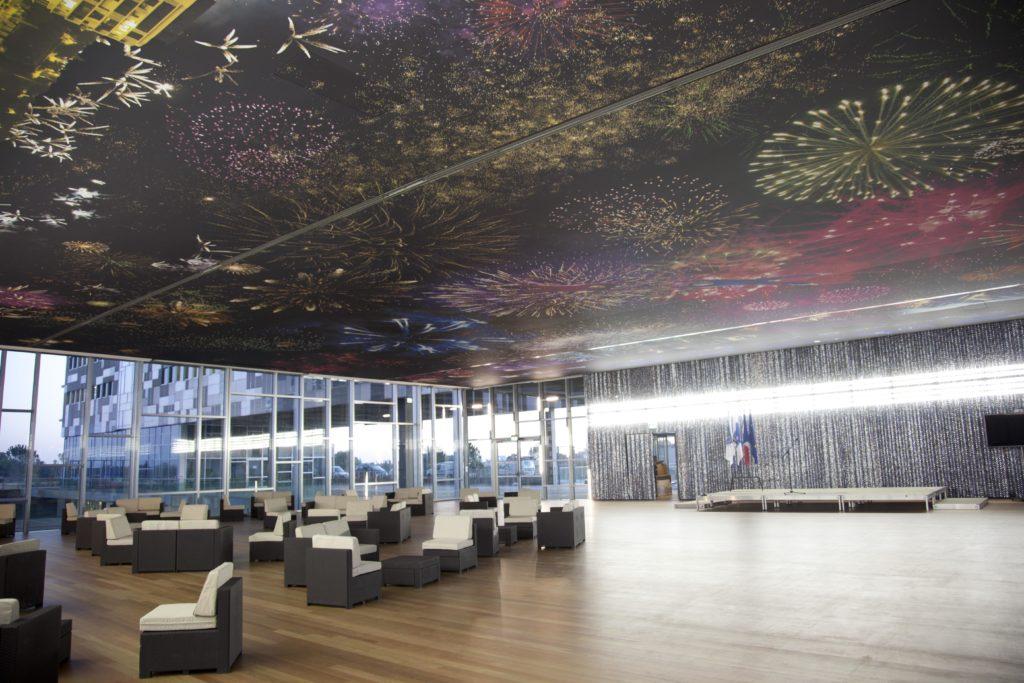 Photo d'un plafond acoustique imprimé avec des visuels de feux d'artifice dans la salle de réception de l'hôtel de ville de montpellier