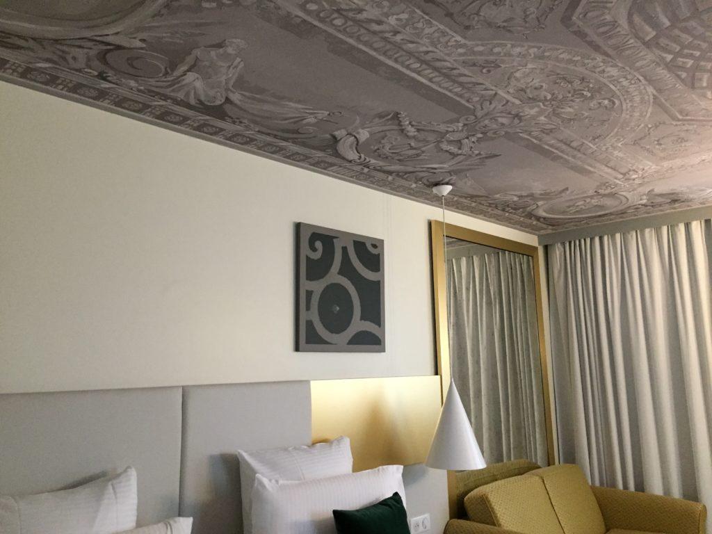 Photo du plafond d'une des chambres de l'Hôtel Le Louis avec un visuel représentant une peinture d'un plafond avec moulures