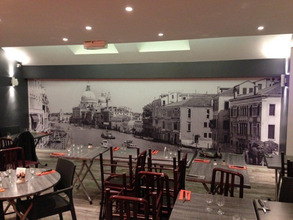Photo d'un mur imprimé avec une vue d'Italie, dans une salle de restaurant inter-entreprise