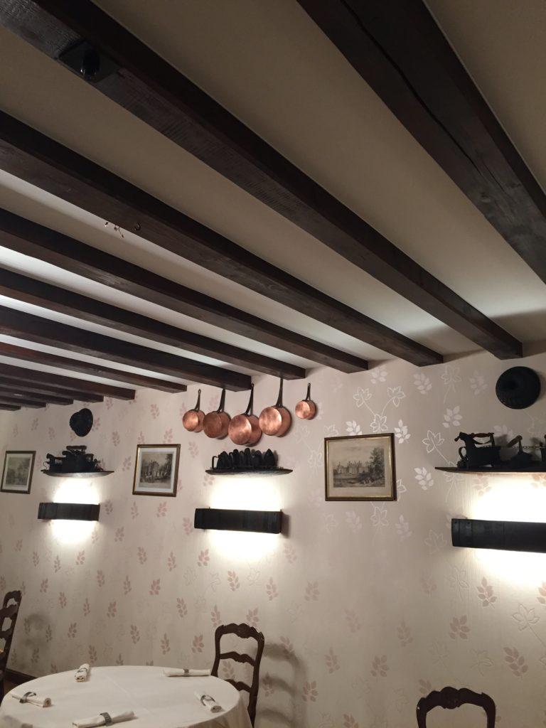 Vue d'un plafond acoustique blanc entre poutres dans une salle de l'Auberge Au vieux Presoir