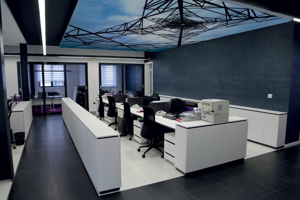 photo d'un espace de bureau en open space avec un cadre acoustique suspendu avec un motif vue du dessous de la tour eiffel