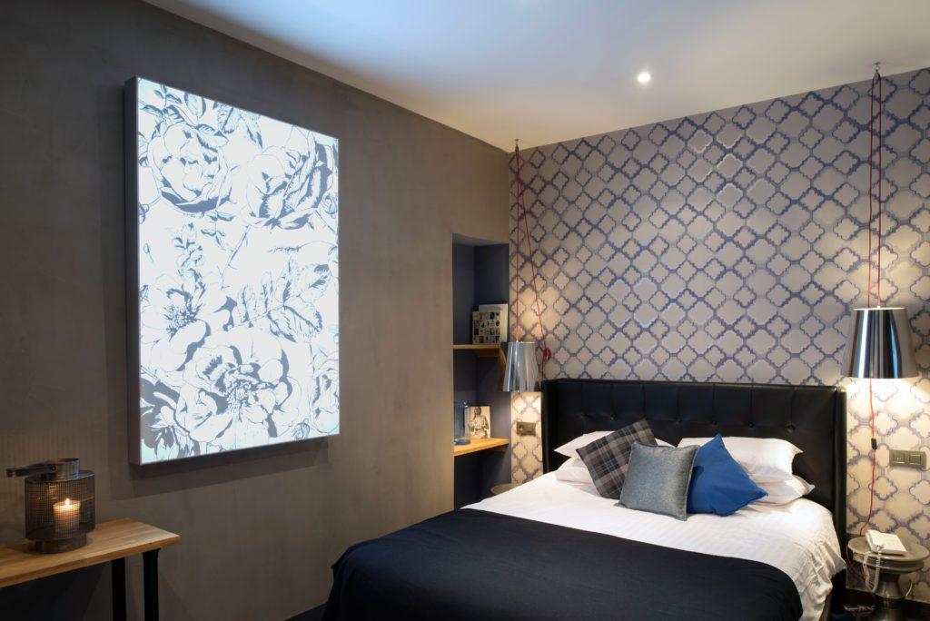 photo d'un cadre rétroéclairé avec un visuel de roses noir et blanc dans une chambre d'hôtel