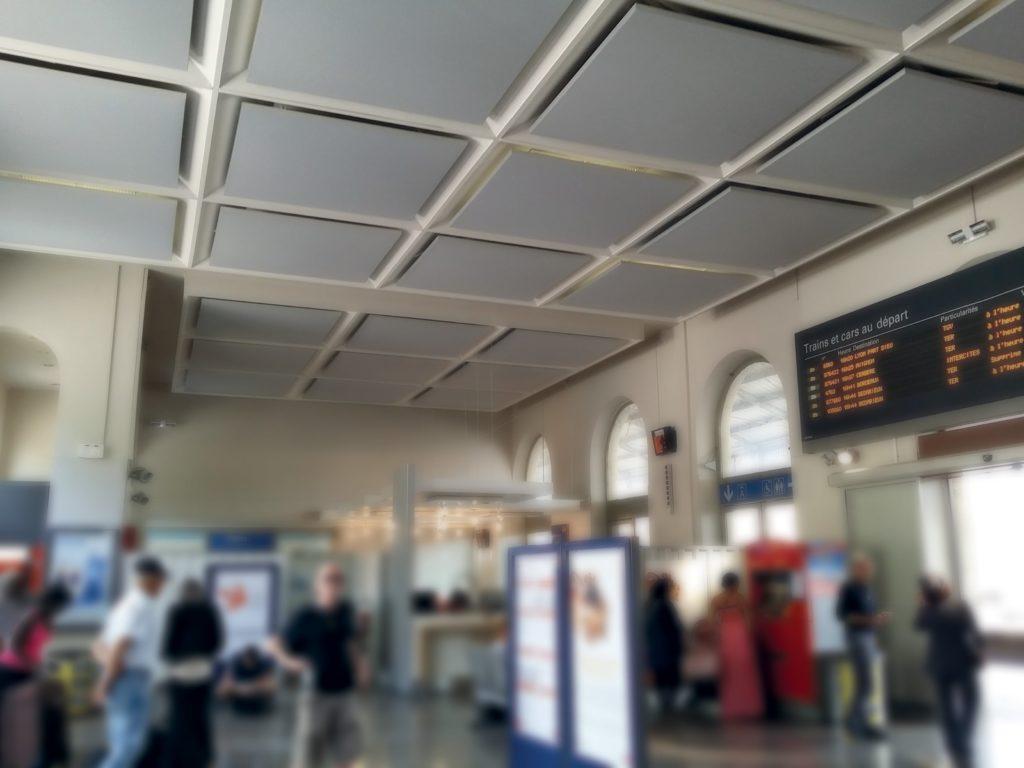 photo d'un hall de gare avec des cadres acoustiques coloris brun fixés au plafond