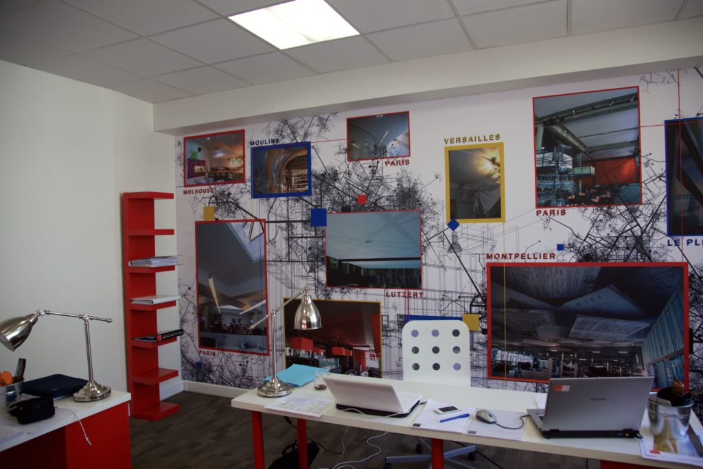 photo d'un mur imprimé dans un bureau avec un visuel cartographié des différentes réalisations de l'entreprise