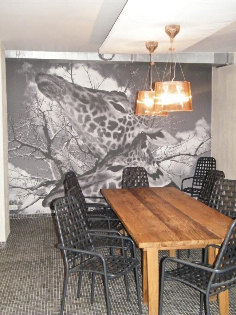 photo d'une toile imprimée en noir et blanc avec des têtes de girafe dans une salle à manger