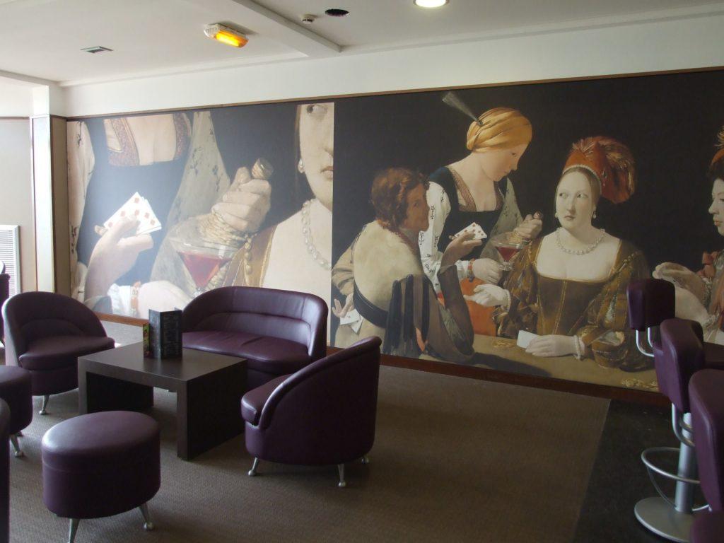 photo d'un mur imprimé avec le tableau de Georges de La Tour, le tricheur à l'as de carreau