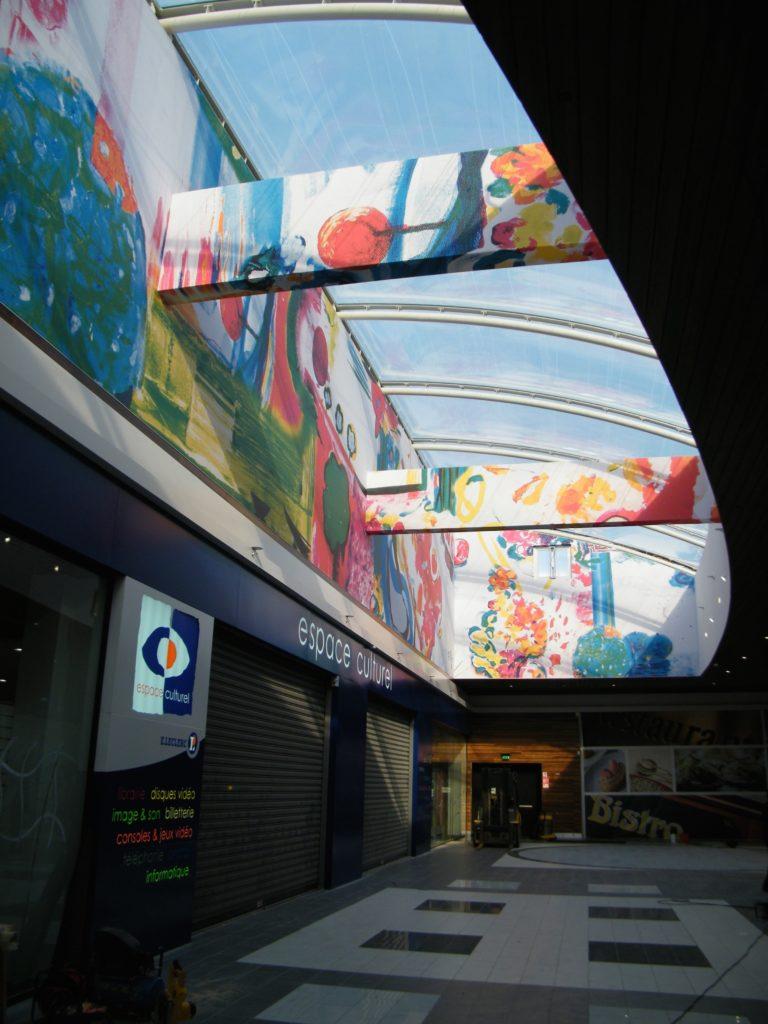photo d'une galerie de centre commercial avec toiles imprimées multicolores