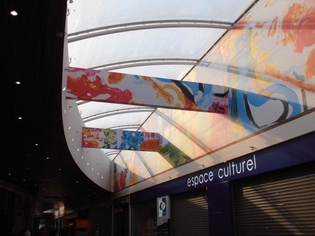 Photo d'un mur et poutres imprimé devant l'espace culturel de la galerie commerciale d'un centre E. Leclerc