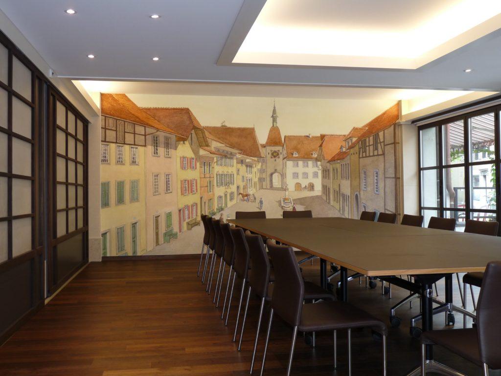 Photo d'une salle de séminaire dans un hôtel avec un mur imprimé à partir d'une aquarelle représentant la place du village