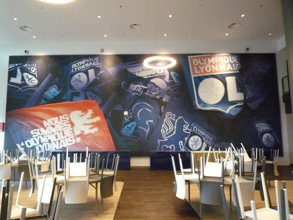 Photo d'un mur imprimé avec le visuel de l'Olympique Lyonnais dans une des loges VIP du Groupama Stadium, Lyon