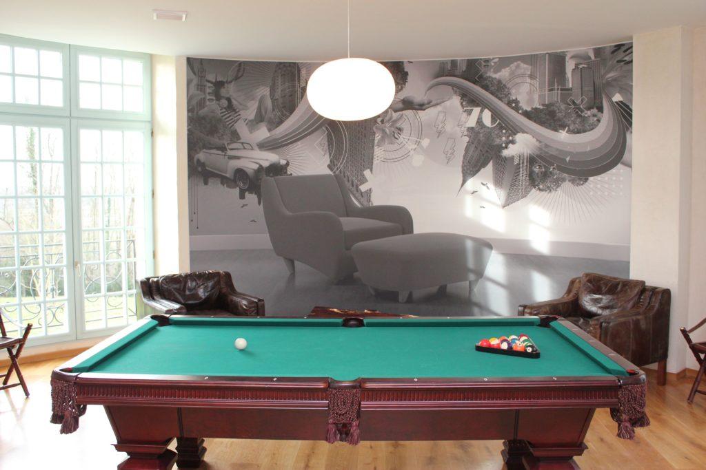 Photo d'une salle de détente avec un billard et un mur imprimé effet trompe l'oeil avec un fauteuil
