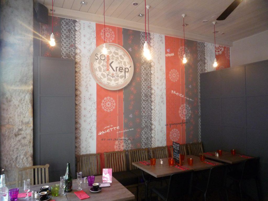 photo d'une salle de restaurant avec un mur imprimé de rayures esprit dentelle