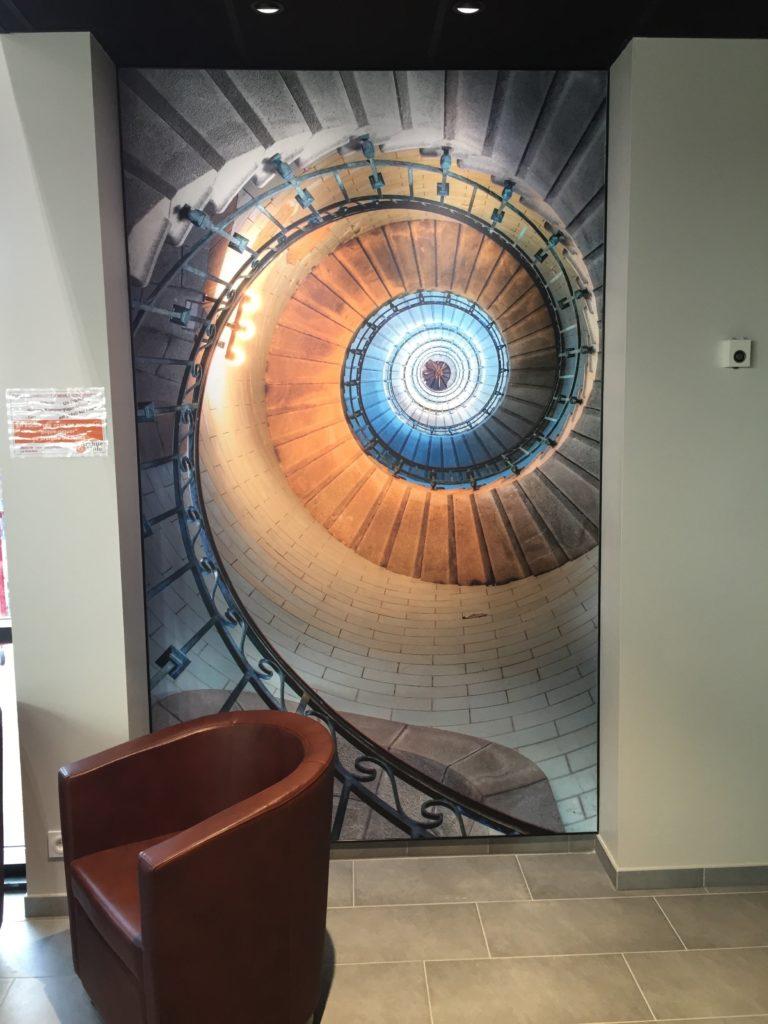 Photo d'un mur imprimé avec un visuel d'escalier en colimaçon