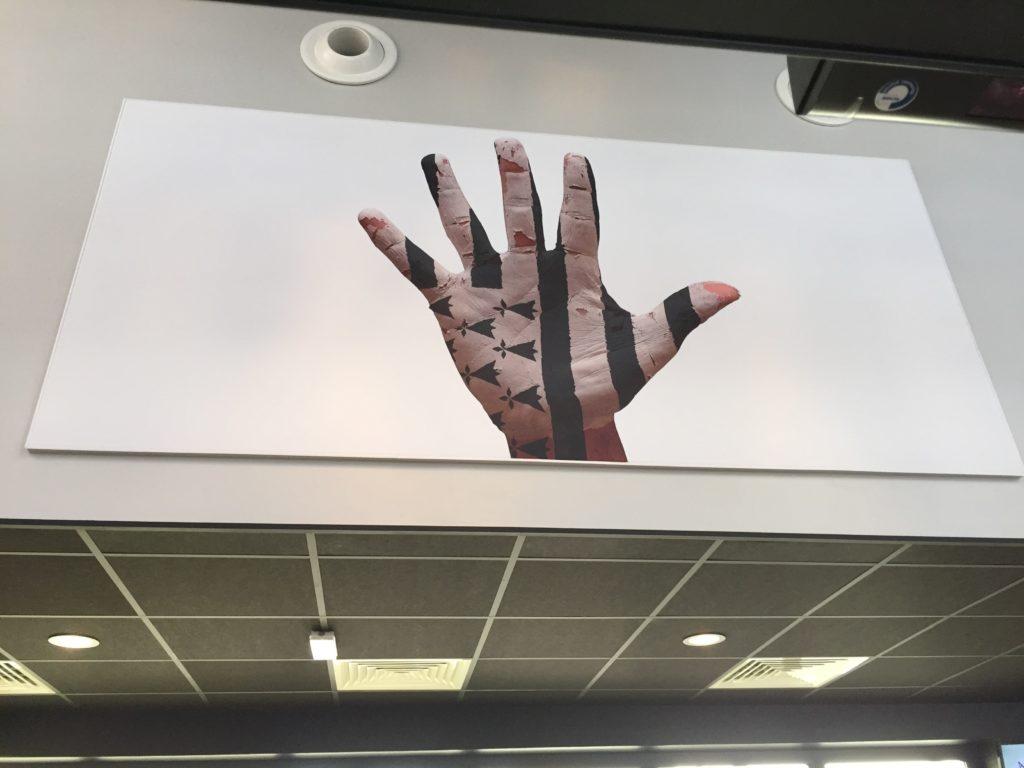 Photo d'un haut de mur avec une toile imprimée d'un visuel main avec le drapeau breton