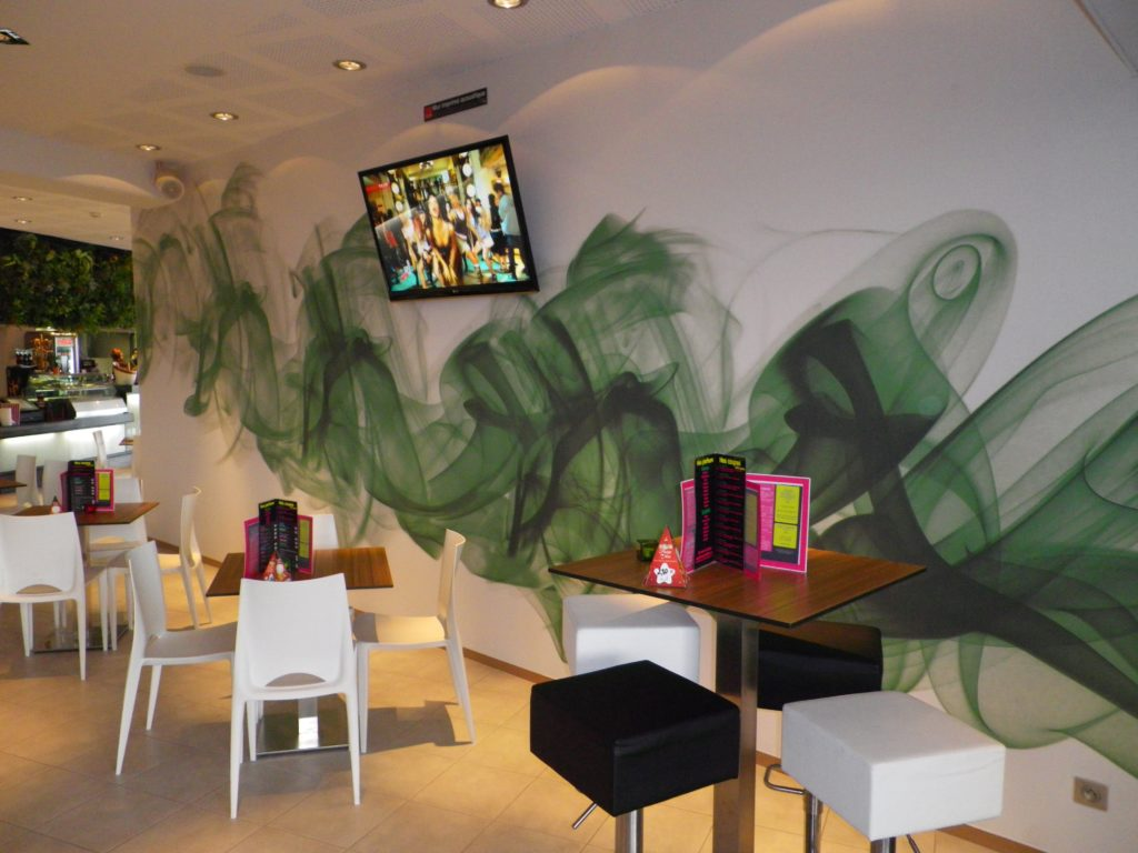 Photo d'un mur imprimé dans une salle de restaurant, avec un visuel de fumée verte