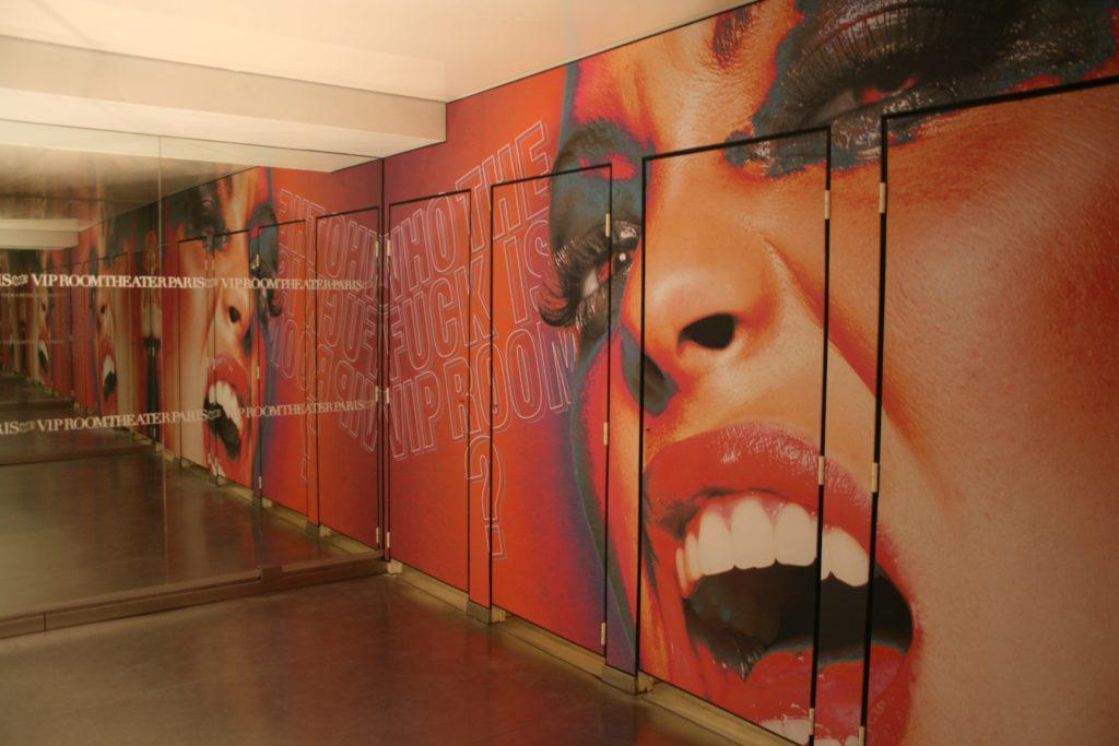 Photo des sanitaires du VIP room avec des murs et portes imprimés avec un visuel de femme