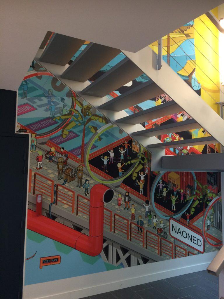 photo d'un mur imprimé effet pixel art dans une montée d'escalier