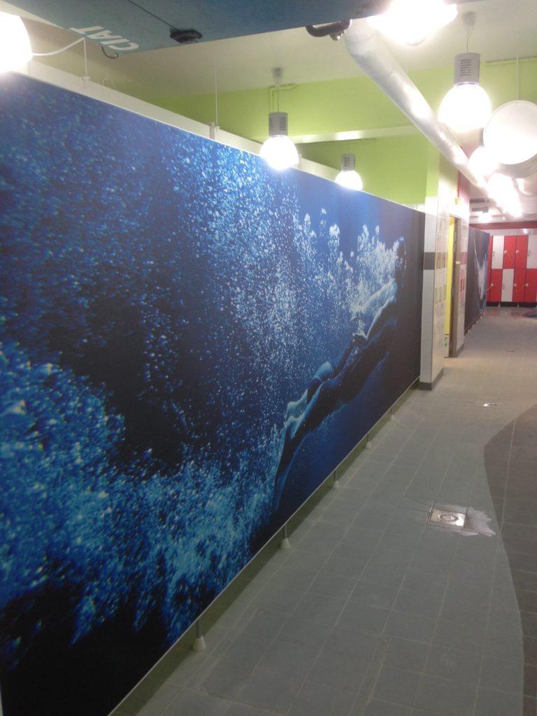 Photo d'un mur imprimé dans un vestiaire d'une piscine avec un visuel d''un homme nageant sous l'eau