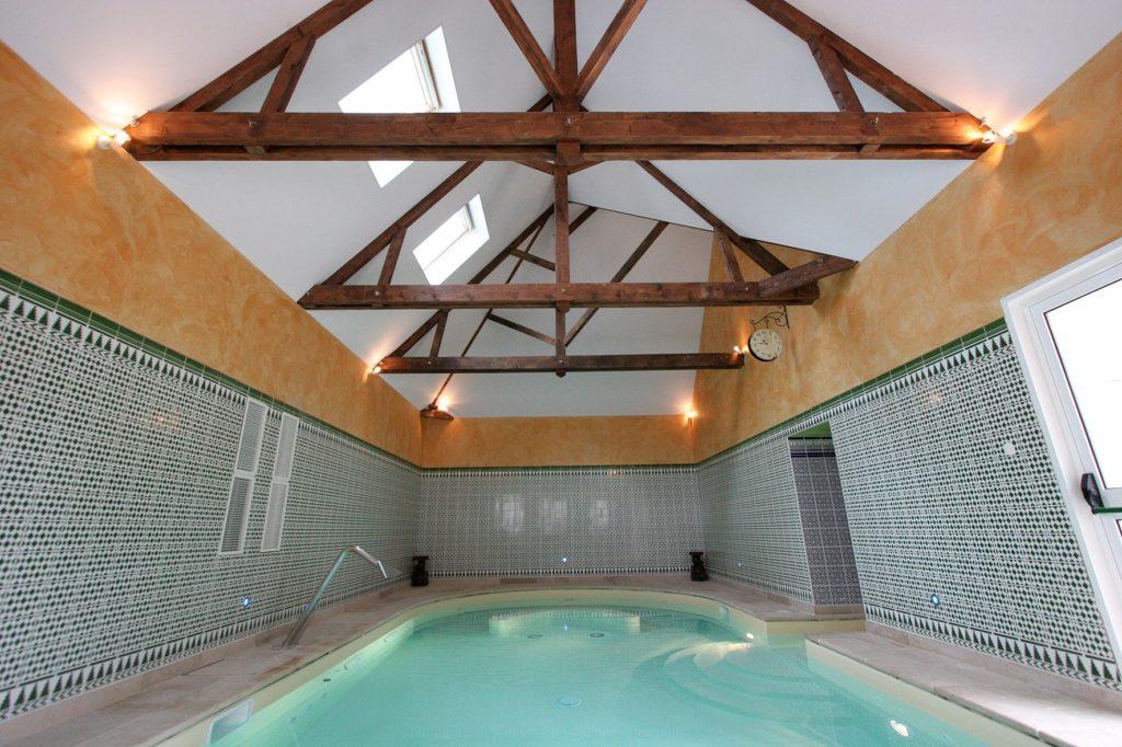 Photo d'un plafond tendu a froid blanc sous rampant au dessus d'une piscine privée