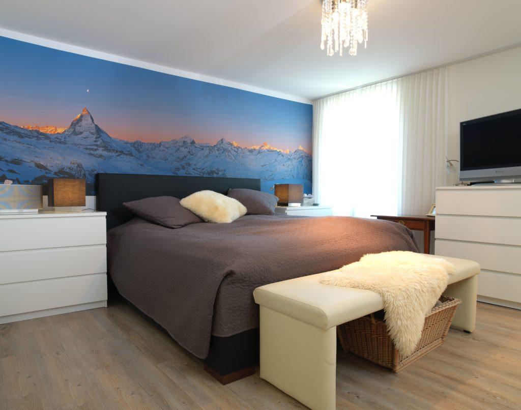Photo d'une chambre à coucher avec un mur imprimé d'un visuel de montagne en tête de lit.