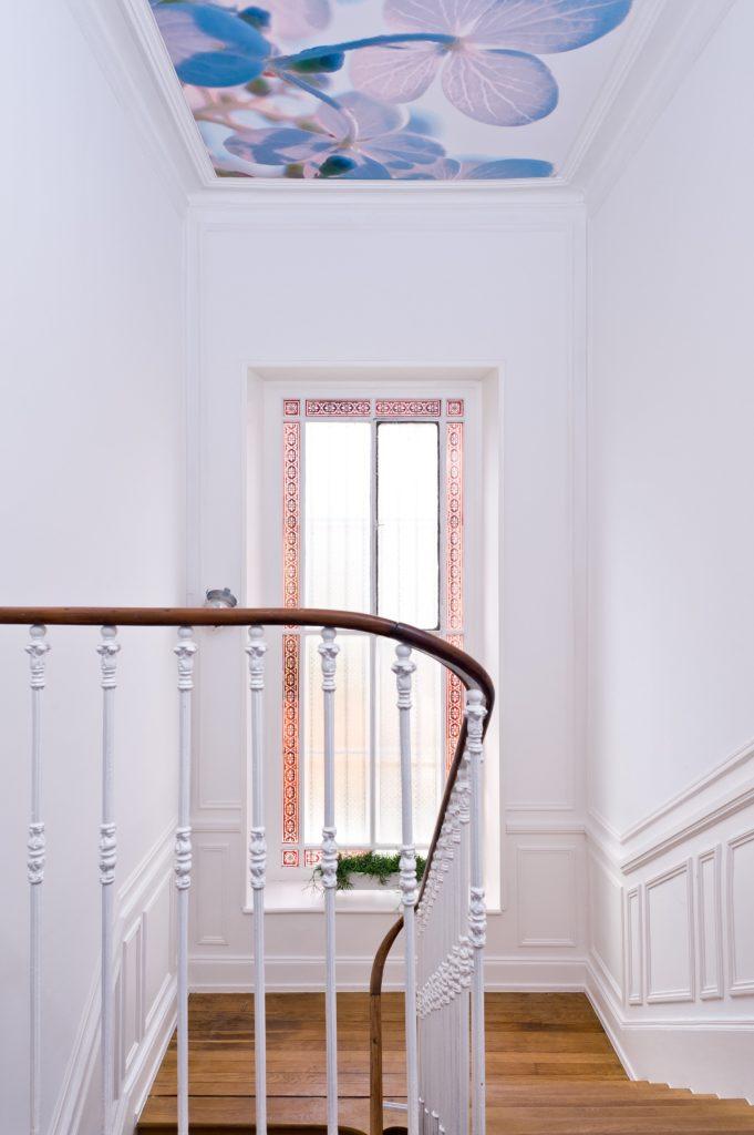 Photo d'un plafond imprimé dans une montée d'escalier avec un visuel de fleurs