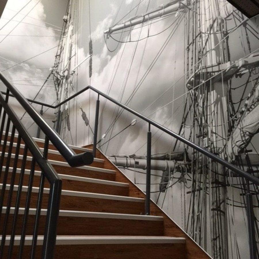 Photo d'un mur imprimé dans une montée d'escalier acec un visuel de mâts de bateau