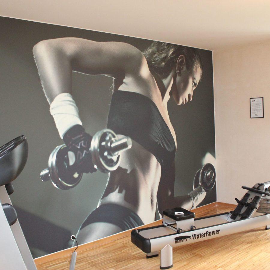 photo d'un mur imprimé avec une un corps de femme portant des haltères