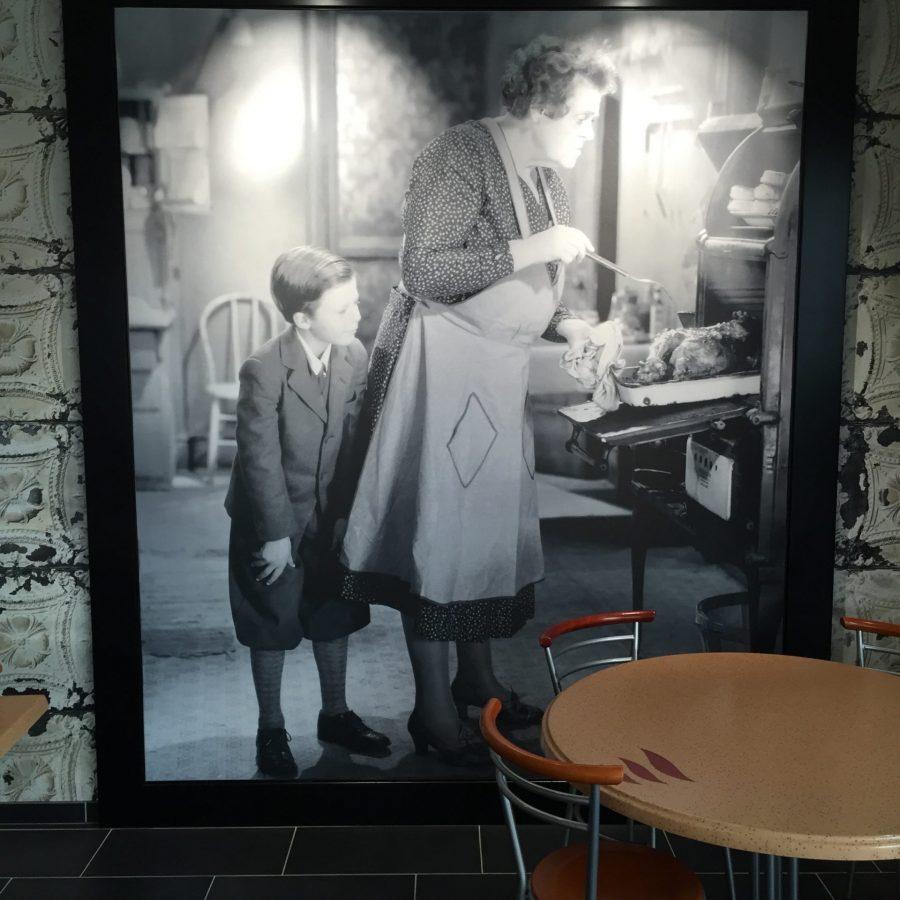 photo d'un mur imprimé en n&b avec une photo d'une femme sortant un poulet du four et de son petit-fils qui la regarde