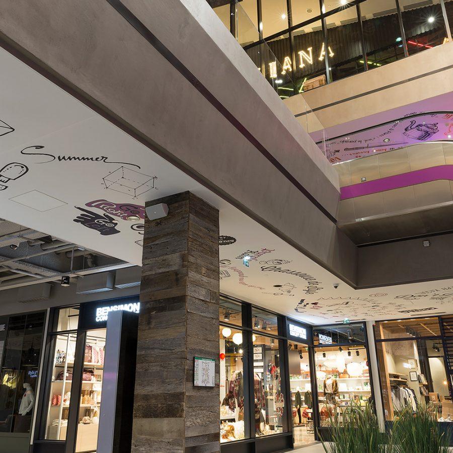 Photo des plafonds acoustiques imprimés avec des design au trait dans le centre commercial VILL'UP à Paris